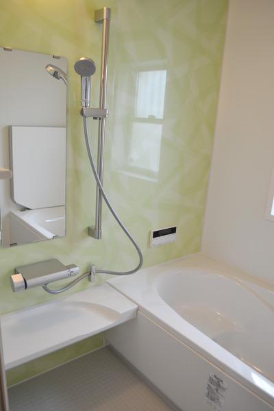 ミントグリーンの壁が爽やかな浴室