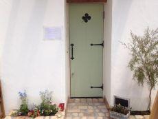 グリーン色の扉とレンガ使いがかわいいエントランス