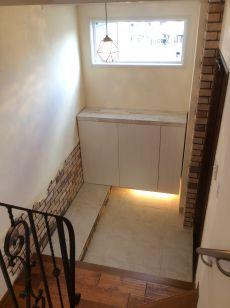 階段から臨む玄関は、様々な素材と色が調和してなんとも味ある眺めです