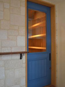店内がよく見えるブルーの店舗入口扉