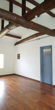 ブルーの扉と白い壁に小窓と梁のあるナチュラルリフォーム